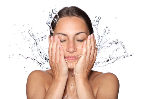 Lady cleansing or washing her acne-prone face