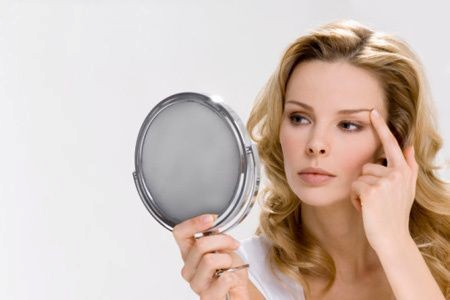 Lady in mirror looking at eye area