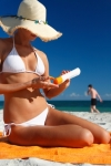 Lady applying sunscreen on beach